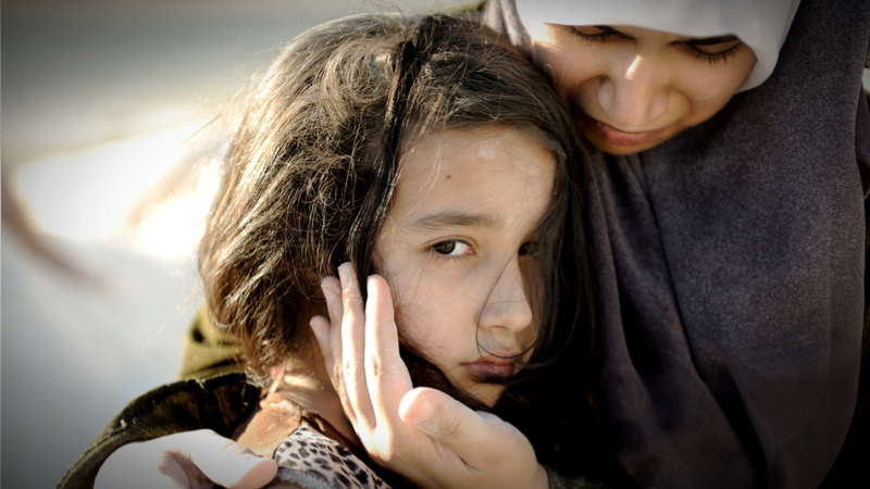 Refugee woman holds sad girl